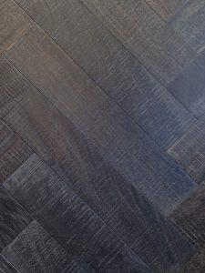 Deze visgraat vloer is bezaagd en zwart geolied.